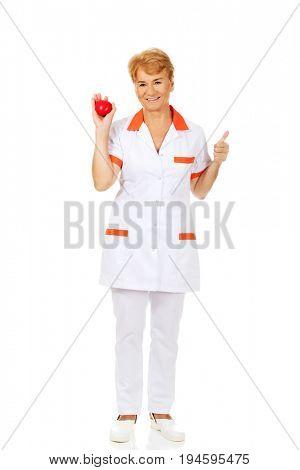 Smile elderly female doctor or nurse holding red toy heart
