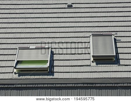 Attic Skylights with Shutters and small solar panels. House Attic Roof Blinds Sun Protection Exterior. Protection Against Sun and Heat as Energy Saving.