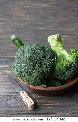 Fresh broccoli in a wooden bowl on wooden table rustic style