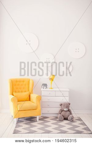 Modern interior with white and yellow colors. Yellow soft armchair ear white bedside. Comfort chair. Armchair with fabric upholstery.