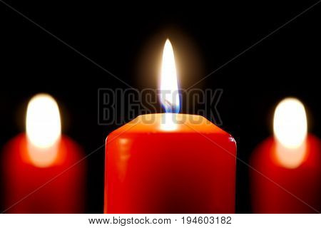 Three burning red candles isolated on black. One candle in focus