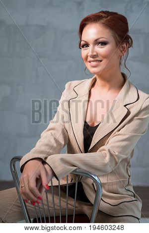 Beautiful red haired woman in nice beige pantsuit sitting on the chair with a charming smile studio portrait
