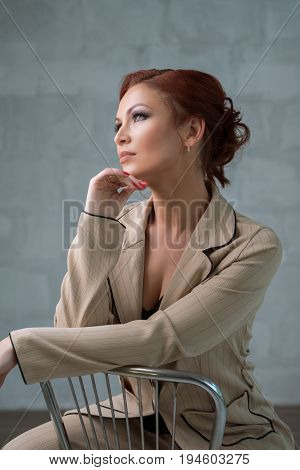 Beautiful red haired woman in nice beige pantsuit sitting on the chair with a romantic look studio portrait
