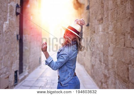 Young woman in jeans and hat dancing in sunset on old narrow streeet