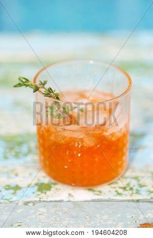 Alcohol orange cocktail on turquoise background, close up