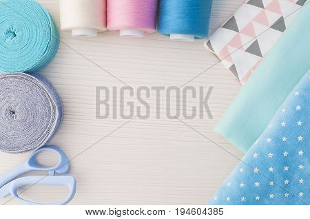 Sewing kit. Thread blue, pink, beige, cloth fabric, scissors,rolls ribana grey and menthol