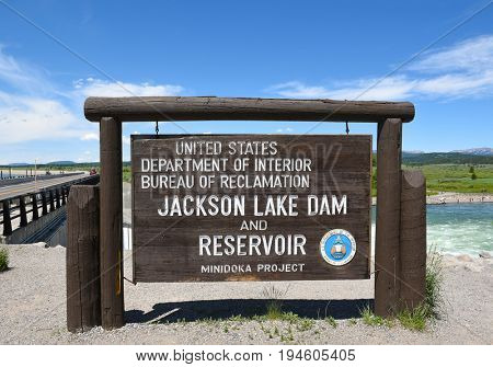 JACKSON HOLE, WYOMING - JUNE 26, 2017: Jackson Lake Dam sign. Built in 1911 in Grand Teton National Park, it has enlarged the natural lake that is primarily fed by the Snake River.