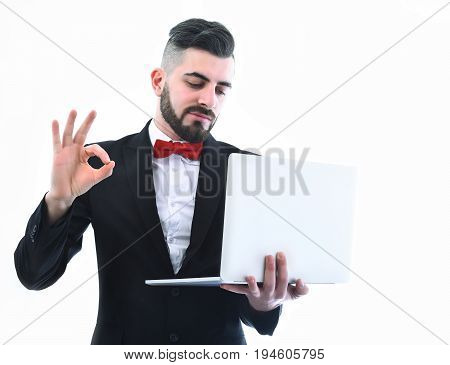 Businessman or project manager with smile on his face and beard shows OK sign and looks at white laptop isolated on white background copy space. Concept of success and high tech era
