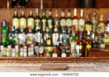 coaster under glass on blurred bar background. wooden old desk and bar on the blured background of buttels on restaurant or pub
