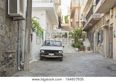 Elounda, Crete, Greece - June 16, 2017: Old rusty white car parked in the street