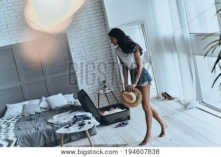 Getting ready for summer vacation. Full length of beautiful young woman holding sun hat while walking in the bedroom