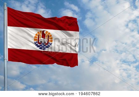 National flag of French Polynesia on a flagpole in front of blue sky.