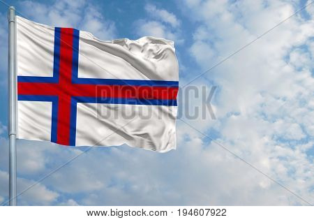 National flag of Faroe Islands on a flagpole in front of blue sky.