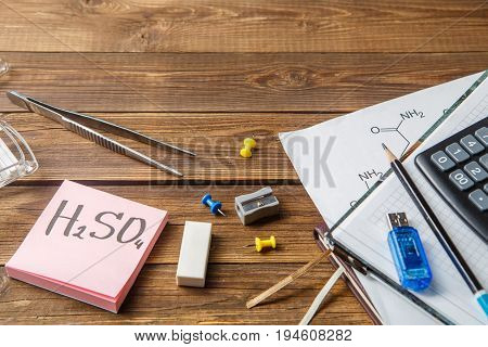 Chemical flasks, tweezers, keyboard, notebooks on a wooden table with copyspase. Educational concept.