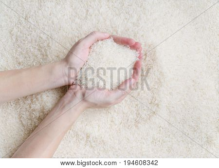 Female hand scooping raw white jasmine rice over texture pattern background the new soft rice grain grown in Thailand (southeast asian country) good for cooking asian dishes (selective focus)