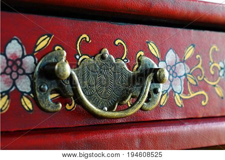 Vintage Furniture Handle On A Red Box With A Floral Pattern.