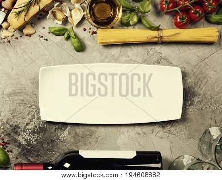 Italian food background with ravioli, vine tomatoes, basil, spaghetti, spinach, onion, parmesan, olive oil, garlic, peppercorns, rosemary and wine. Slate background
