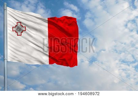 National flag of Malta on a flagpole in front of blue sky.