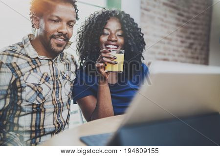 Smiling young african american couple having online conversation together via touch tablet at the morning in living room.Blurred background.Flare