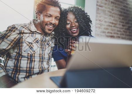Happy young african american couple having online video chat together via touch tablet at the morning in living room.Blurred background.Flare.Horizontal