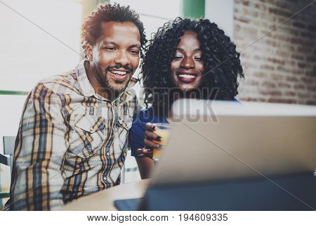 Happy young african american couple having online video chat together via touch tablet at the morning in living room.Blurred background.Flare.Cropped
