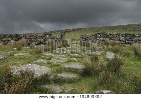 Stones and ancient wall in dartmoor landscape on a clouded grey day