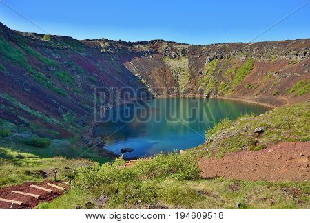 View into the Kerid crater with its blue lake at the bottom as a part of the famous Golden Circle in western Iceland