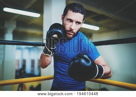 Young boxer man fighter in boxing gloves.Boxing man ready to fight. Boxing, workout, muscle, strength, power - the concept of strength training.Horizontal.Blurred background