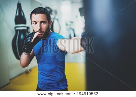 Young muscular kickboxing fighter practicing kicks with punching bag.Boxing on blurred background.Concept of a healthy lifestyle.Horizontal