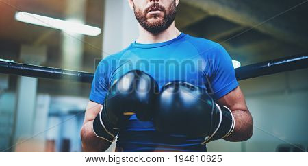 Young man in boxing gloves. Young Boxer fighter over blurred background.Boxing man ready to fight. Boxing, workout, muscle, strength, power - the concept of strength training.Horizontal wide.Cropped