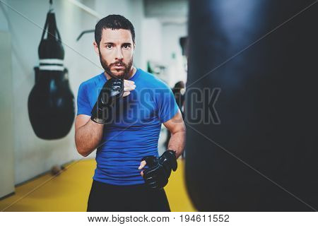Concept of a healthy lifestyle.Young athlete fighter practicing kicks with punching bag.Kick boxer boxing as exercise for the fight.Boxer man hits punching bag.Horizontal