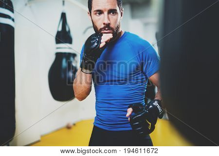 Concept of a healthy lifestyle.Young muscular man fighter practicing kicks with punching black bag.Kick boxer boxing as exercise for the fight.Boxer hits punching bag in gym.Horizontal