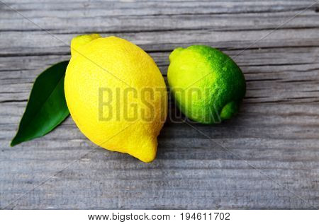 Fresh ripe organic lemon and lime fruits on old wooden table.Lemon and lime.Diet or aromatherapy concept.Copy space.
