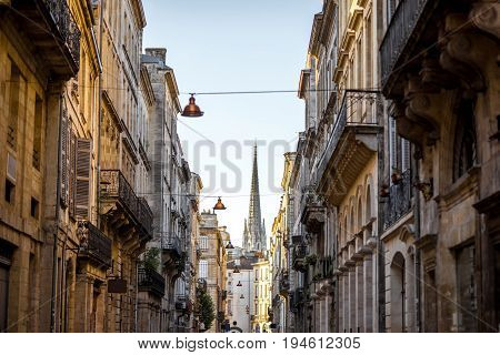 Beautiful morning street view with old buildings and tower of saint Michel cathedral in Bordeaux city, France