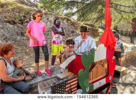 San Leo Italy - June 18 2017: Unidentified old musician with on a barrel organ is teaching the children their craft.