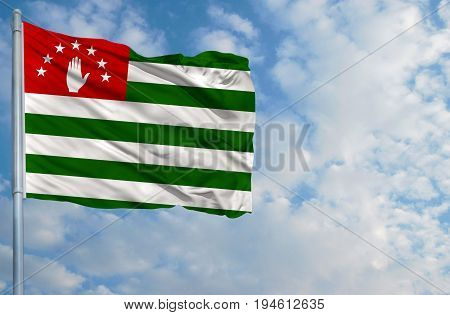 National flag of Abkhazia on a flagpole in front of blue sky.