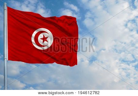 National flag of Tunisia on a flagpole in front of blue sky.