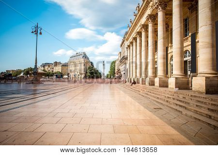 View on the square with Grand Theatre building in Bordeaux city, France. Long exposure image technic with motion blurred people and clouds