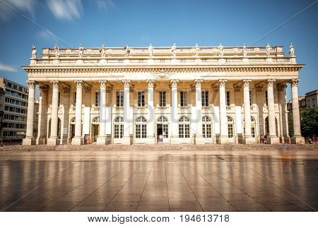 View on the facade of Grand Theatre building in Bordeaux city, France. Long exposure image technic with motion blurred people and clouds