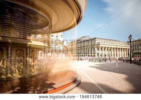 View on the square with carousel and Grand Theatre building in Bordeaux city, France. Long exposure image technic with motion blurred carousel and clouds