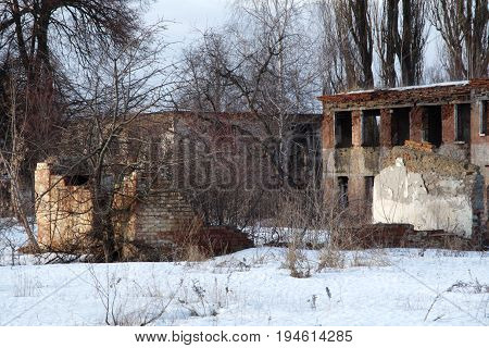 Ruined house with many window proies. The plaster was scolded and the red brick was visible.
