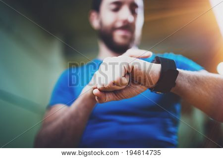 Young smiling athlete checking burned calories on electronic smart watch application after good indoor workout session in fitness gym.Blurred background.Flares effect