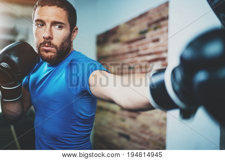Young man boxing workout in fitness gym on blurred background.Athletic man training hard.Kick boxing concept.Horizontal