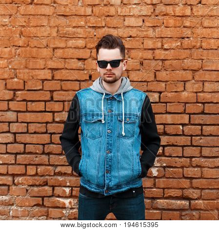Handsome Hipster Guy In A Denim Jacket Near A Brick Wall