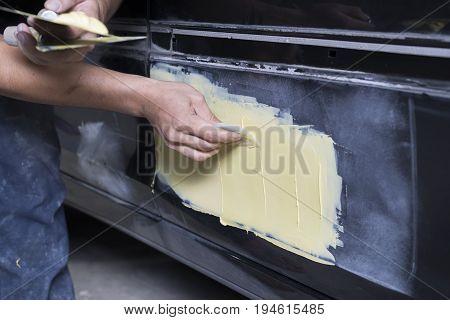 Auto body repair series: Mechanic applying putty filler