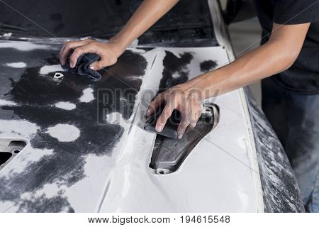 Auto body repair series: Closeup of mechanic wet-sanding car bonnet