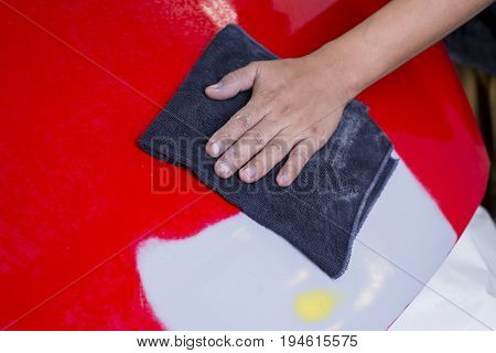 Auto body repair series: Cleaning red car bonnet before repaint
