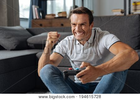 Another win. Entertaining witty handsome man looking satisfied while spending his day at home and playing video games