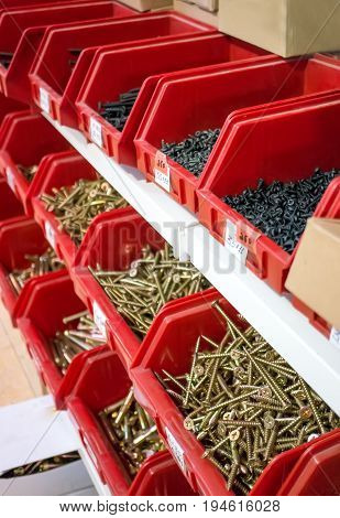 Screws, dowels and nails in red boxes in the mini market for sale.