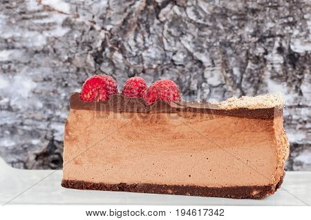 Lateral view of low carb, home made, sugar free, no bake raspberry chocolate cheesecake slice